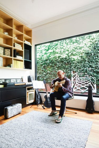 """The home office doubles as a studio for Bill, a keen musician. The wooden sculpture in the garden came with the house. """"We loved it so much we made sure it was kept,"""" says Christine."""