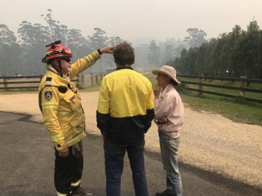 Captain John Lardner speaking with Graham and Bec Jones at the entrance to their property in Nana Glen on Tuesday.