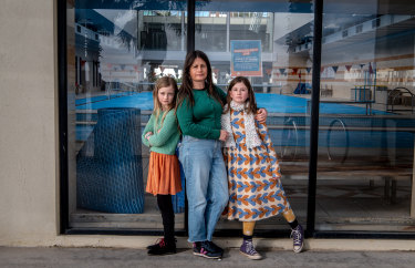 Kathryn Bowen and her daughters Isidora, 8 and Mathilde, 11, outside the St Kilda Sea Baths, where they have swimming lessons when public pools are open.