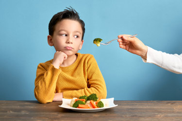 Child unhappy eating vegetables.