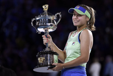 A smiling Sofia Kenin holds the Daphne Akhurst Memorial Cup after defeating Spain's Garbine Muguruza in the Australian Open final on Saturday night.