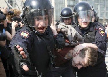 Police detain a protester.