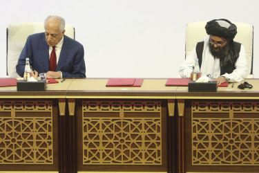 US peace envoy Zalmay Khalilzad, left, and Mullah Abdul Ghani Baradar, the Taliban group's top political leader sign a peace agreement.