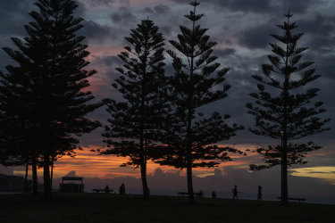 People exercise at Maroubra Beach in Sydney's east as the fog begins to roll in.