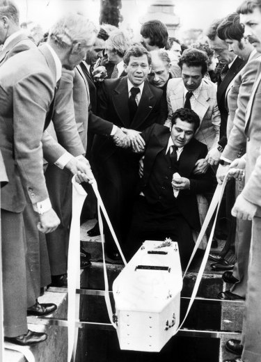 Sam Gulle sobbing as the coffin of his infant child is lowered into a grave.