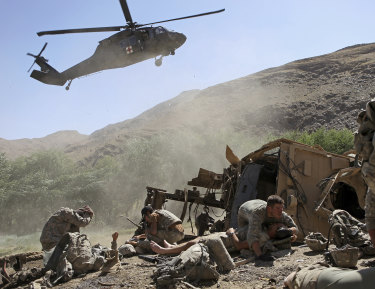 An Army soldier covers an injured comrade as a helicopter lands to evacuate the wounded after their armored vehicle hit an improvised explosive device in the Tangi Valley of Afghanistan's Wardak Province in 2009.