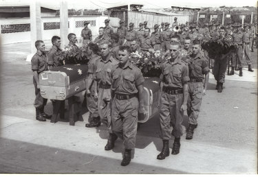 Australian pallbearers carry the coffins of three of their Ist Battalion comrades into a chapel for a memorial service in Saigon. The soldiers were killed in the June 26 incident.