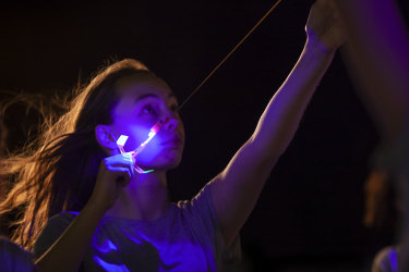 A child shoots a flying LED toy into the air in Angelica Mesiti's Assembly.