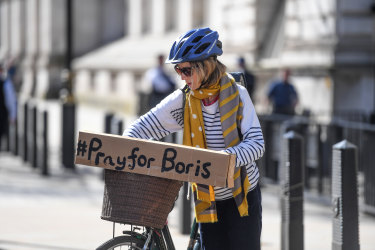 """A cyclist with a """"Pray for Boris"""" sign in London."""
