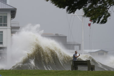 A man takes pictures of high waves along the shore of Lake Pontchartrain as Hurricane Ida approaches.