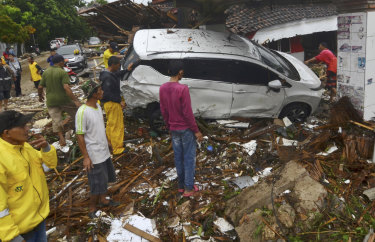 People inspect the wreckage of a car swept away by a tsunami.