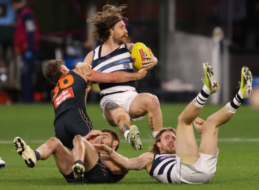 Geelong's Zach Tuohy is tackled by Harry Perryman.