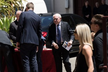 Former prime minister John Howard holding a funeral booklet of John Fordham at St Francis of Assisi's Catholic Church on Friday.