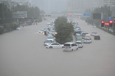 Vehicles are stranded in floodwater near Zhengzhou Railway Station in central China's Henan province.