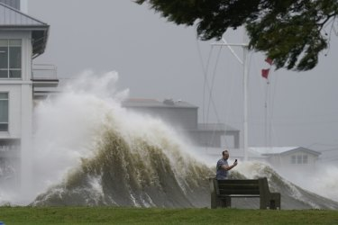 A man takes pictures of high waves along the shore of Lake Pontchartrain in Louisiana as Hurricane Ida nears.  Climate change will lift sea levels everywhere, adding more heat to the oceans.