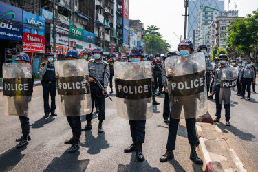 Riot police stand guard as anti-coup protesters march through the streets.