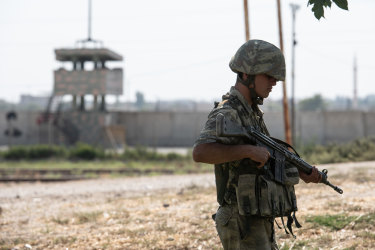 A Turkish soldier patrols on the Turkish side of the border between Turkey and Syria on Wednesday in Akcakale.