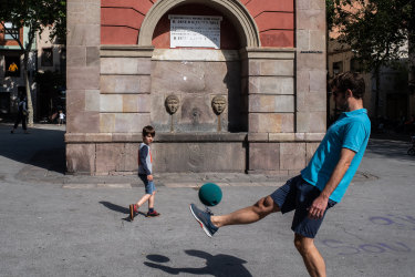 A father and his son play football in Barcelona, Spain.