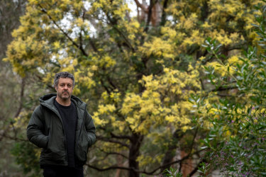 Dylan Martorell by the Yarra River with one of the wattles he has transcribed into music.