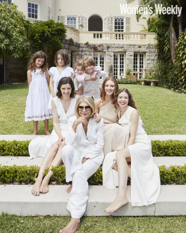 Carla Zampatti with her daughters, Bianca (right) and Allegra Spender, and five of her nine grandchildren.