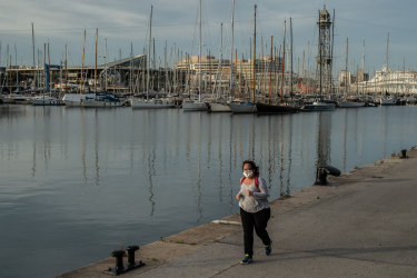 A woman wearing a protective face mask jogs along Barcelona's port.