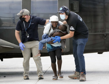 Rescue workers help an injured woman and a boy from a helicopter.