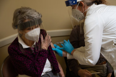 A healthcare worker administers the Pfizer-BioNTech vaccine to an aged care resident in Bloomfield Hills, Michigan, US.