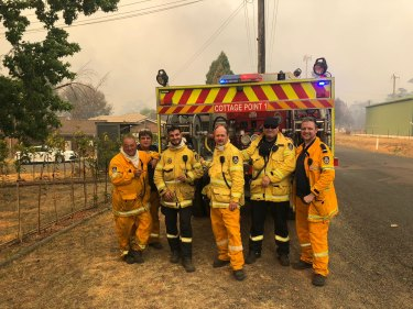 Jon Russell, (second from left, in blue shirt), a captain of the Cottage Point RFS brigade, says at least one member of his crew could be ineligible for theNational Emergency Medal despite active and dangerous service during the 2019-20 bushfire season.