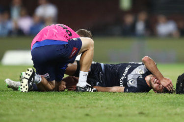 Down and out: Terry Antonis receives attention from Victory medical staff after suffering a knee injury at the SCG on Saturday night.