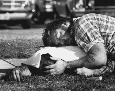 A man grieves over his brother, one of the dead.