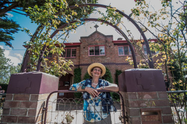 The owner of the former Saint Joseph's Convent in Bungendore, Pamela Orr, stands at its gates.