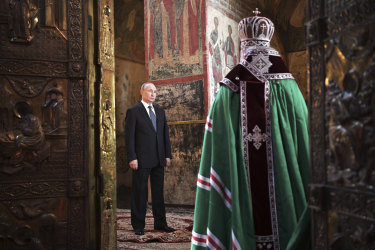 Russian President Vladimir Putin attends a service held by Russian Orthodox Patriarch Krill, right, after the inauguration ceremony in the Kremlin in Moscow.