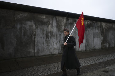 An elderly man with a Soviet flag walks in front of remains of the Berlin Wall.