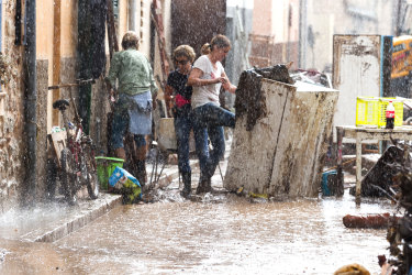 Residents place their damaged belongings on the street under pouring rain.