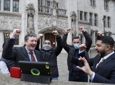 Uber drivers and their union celebrate after hearing the verdict outside the Supreme Court.