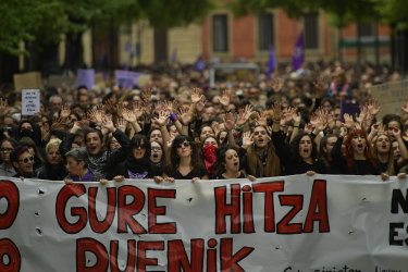 Women hold up a sign reading in basque language, ''Our Word''.