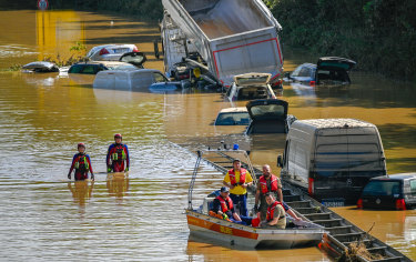 Search and rescue teams are seen on a flooded and damaged part of the highway in a German town.