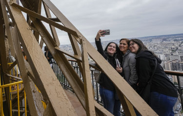 Visitors take a selfie with a phone from the Eiffel Tower.