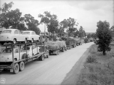 Trucks and drivers stranded on washed out Hume Highway, Wagga Wagga. Taken on 20 July 1956.