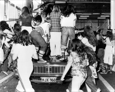 Fans climb a police car when the Bay City Rollers arrived at Sydney Airport in 1975.