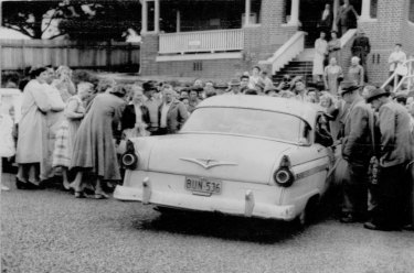 """Crowds gather outside Wyong court today to see Simmonds as he leaves in a car under police escort for Sydney."" November 16, 1959."