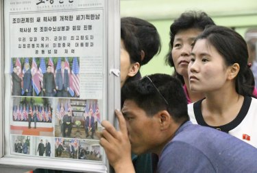 People look at the display of local newspaper reporting the Trump-Kim meeting at a subway station in Pyongyang.