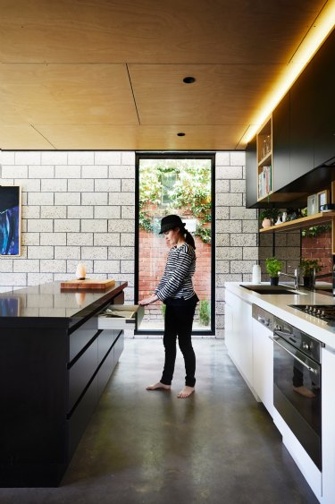 Harriet in the kitchen, where a warm, panelled plywood ceiling softens theindustrial look of the polished concrete floor and honed brick wall.