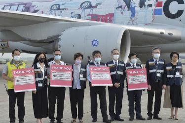 El ministro de Salud de Taiwán, Chen Shih-chung, quinto desde la derecha, posa con tarjetas de agradecimiento después de recibir un envío de vacunas BioNTech.