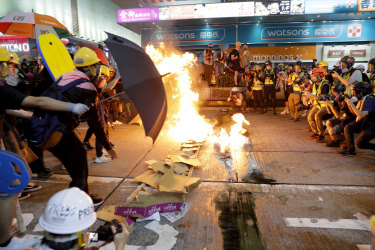 Protesters burn cardboard to form a barrier as they confront with police in Hong Kong.