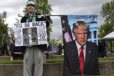 Paul Roblyer from Portland, Oregon, holds a flag of with an image of former President Donald Trump at a second amendment rally on May 1.