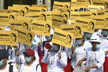 Medicals students display images of deposed Myanmar leader Aung San Suu Kyi during a street march in Mandalay, Myanmar.