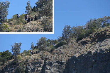 People posing for a photo at Sea Cliff Bridge just 48 hours after a man fell to his death at the same location.