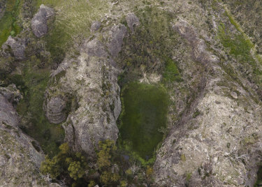 An aerial view of Gooch's Crater near the Gardens of Stone National Park, with larges patches of pink flannel flowers on display.