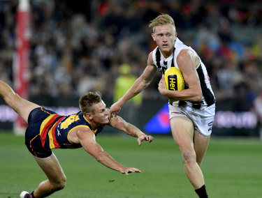 Jaidyn Stephenson of the Magpies gets away from David Mackay.